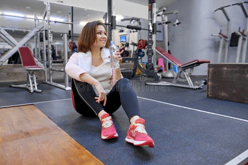 Stående av att le den mogna kvinnan med handdukdricksvatten från flaskan i idrottshall Vård- begrepp för konditionsportålder royaltyfri fotografi