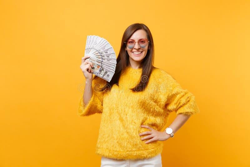 Stående av att le den nätta unga kvinnan i hjärtaglasögon som rymmer packemassor av dollarkassapengar som isoleras på ljust arkivfoto