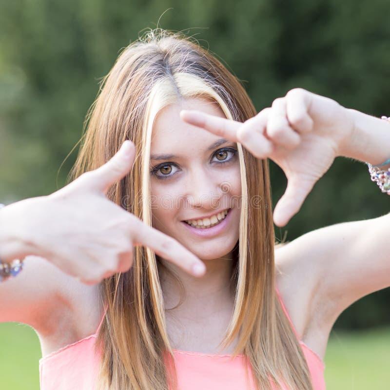 Stående av att le den positiva kvinnadananderamen med henne händer arkivfoto