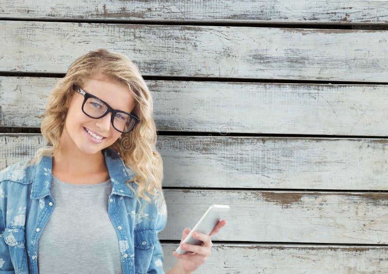 Stående av att le den smarta telefonen för kvinnainnehav mot träväggen arkivfoto