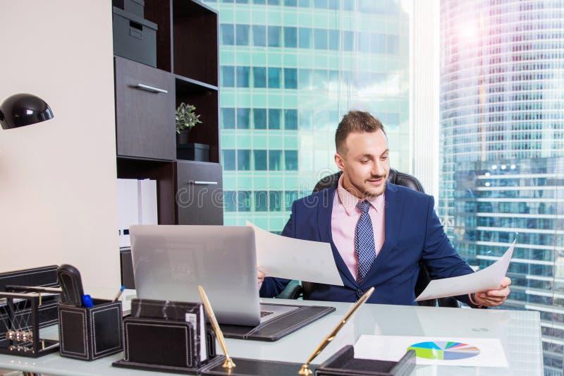 Stående av att le den stiliga affärsmannen som arbetar med dokument, bärbar dator på skrivbordet i modernt kontor royaltyfri bild