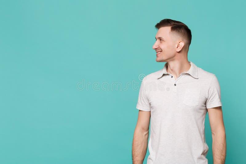 Stående av att le den stiliga unga mannen i tillfällig kläder som står som ser åt sidan isolerad på den blåa turkosväggen royaltyfri bild