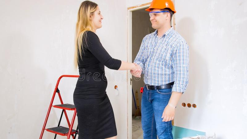 Stående av att le den unga affärskvinnan som skakar händer med den manliga byggnadsarbetaren fotografering för bildbyråer