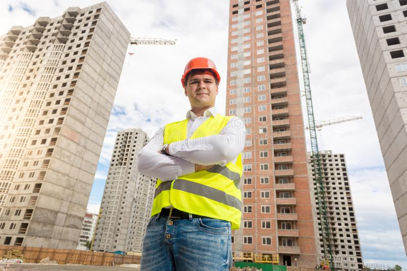 Stående av att le den unga arkitekten i hardhaten som poserar på byggnadsplats arkivbilder