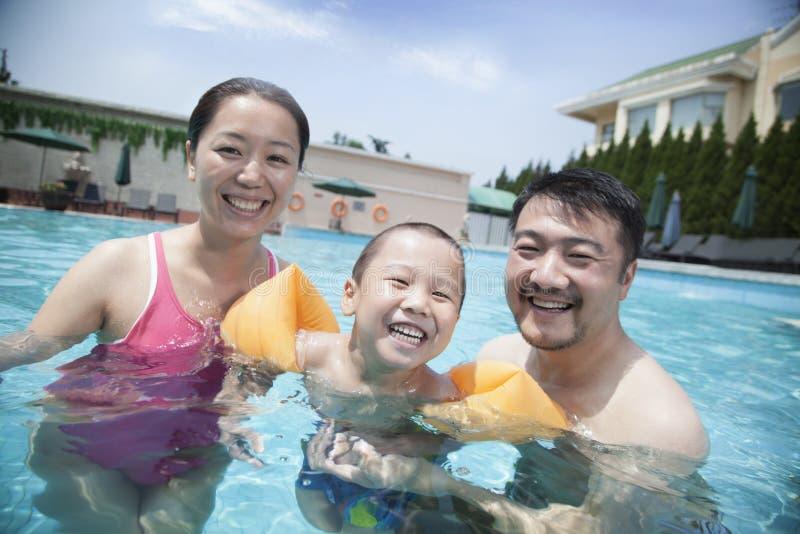 Stående av att le den unga familjen i pölen på semester arkivfoton