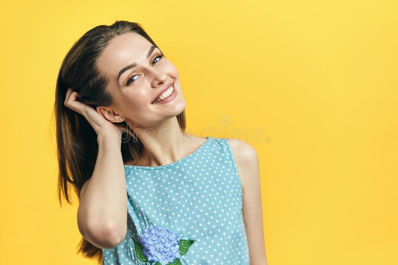 Stående av att le den unga härliga kvinnan som ser kameran som trycker på hår över gul bakgrund royaltyfria foton