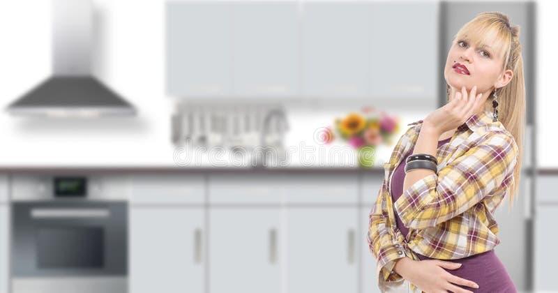 Stående av att le den unga hemmafrun i modernt kök fotografering för bildbyråer