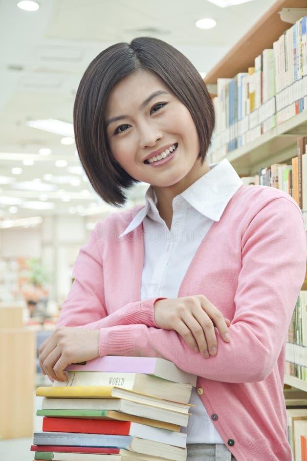 Stående av att le den unga kvinnan i arkivbenägenhet på en bunt av böcker som ser kameran royaltyfria bilder