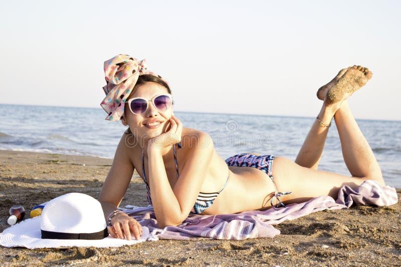 Stående av att le den unga kvinnan i baddräkten som ligger på stranden arkivbilder