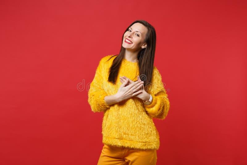 Stående av att le den unga kvinnan i den gula pälströjan som rymmer händer vikta på hjärta, bröstkorg som isoleras på ljust rött royaltyfria bilder