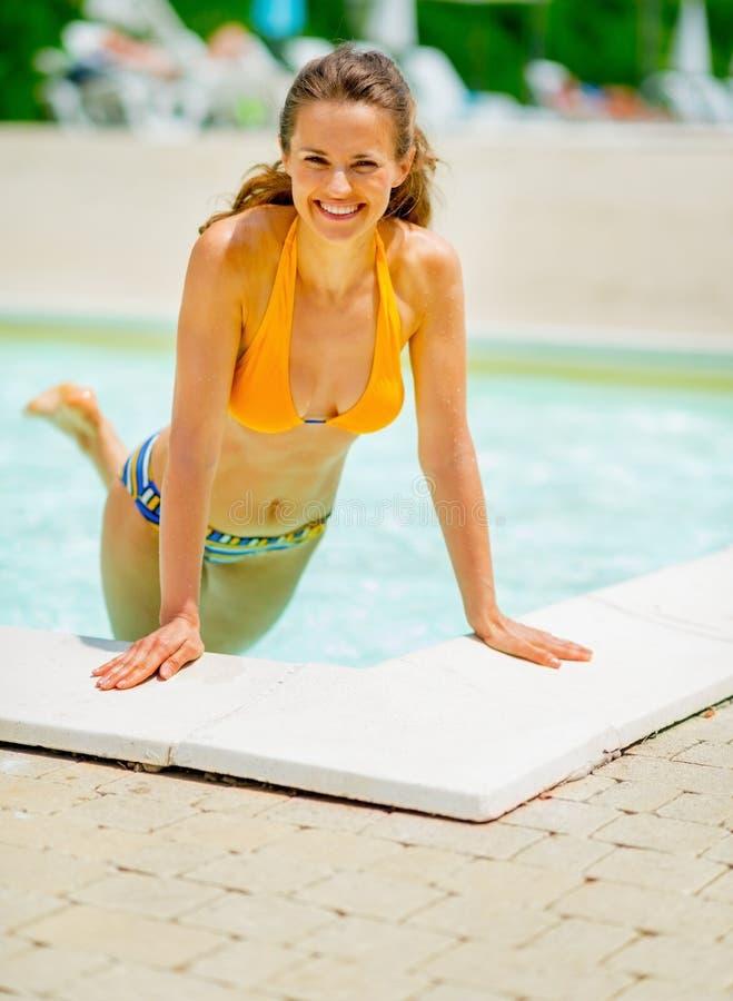 Stående av att le den unga kvinnan i simbassäng royaltyfria bilder