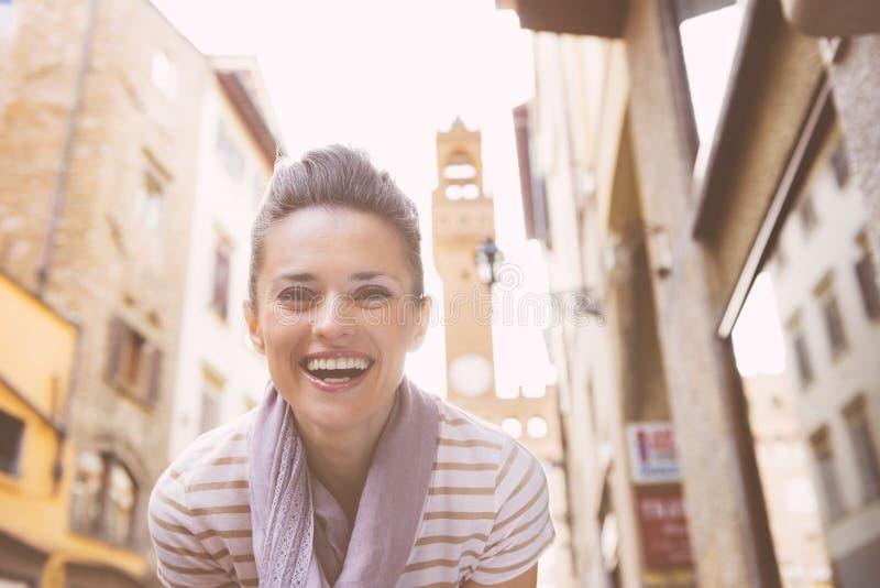 Stående av att le den unga kvinnan inte långt från palazzovecchio royaltyfri bild