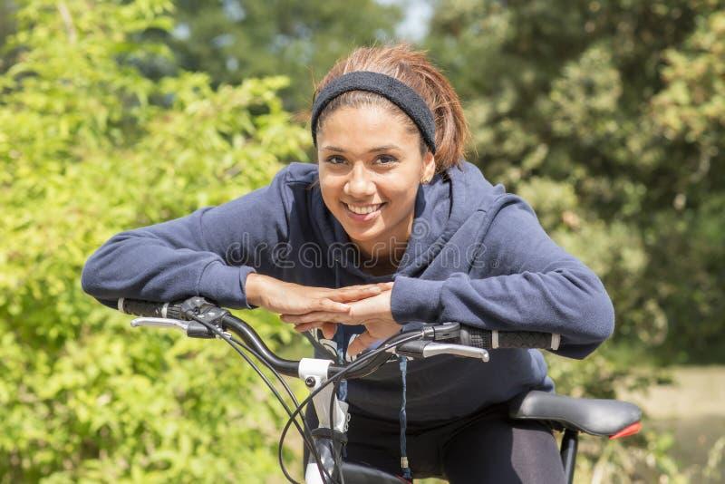 Stående av att le den unga kvinnan som övar med cykeln som är utomhus- arkivbild