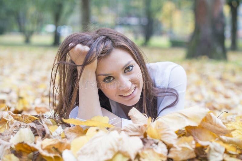 Stående av att le den unga kvinnan som ligger på höstsidor royaltyfri bild