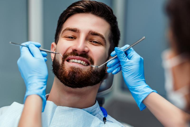 Stående av att le den unga mannen med tandläkaren som rymmer tand- hjälpmedel på kliniken Slapp fokus fotografering för bildbyråer