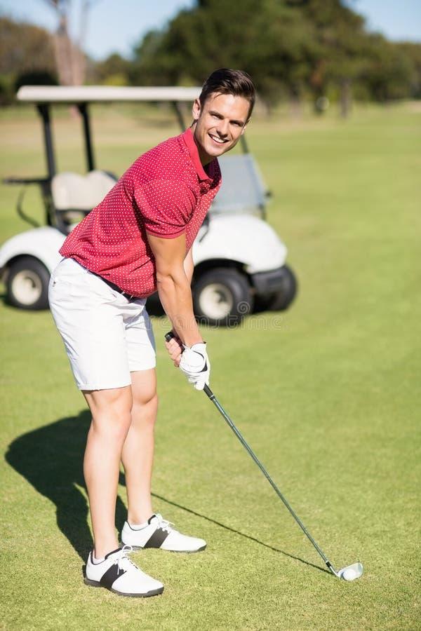 Stående av att le den unga mannen som spelar golf royaltyfria foton