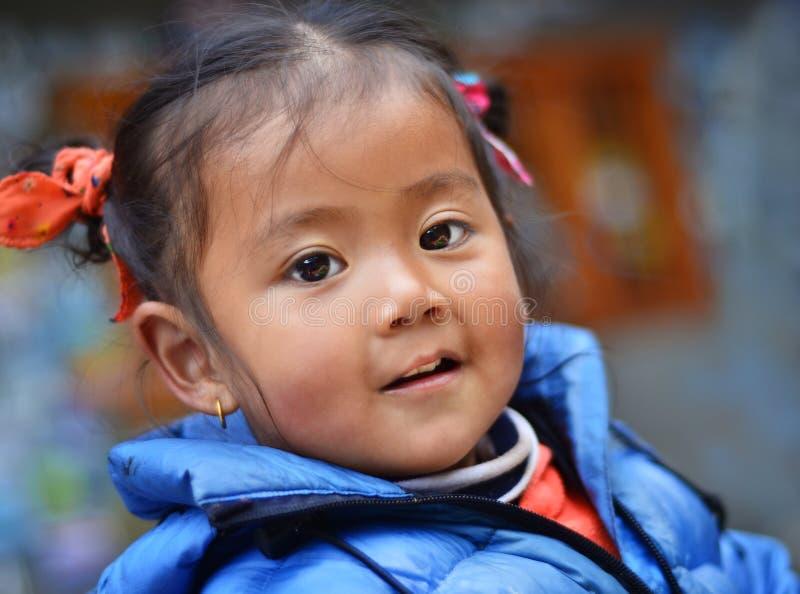 Stående av att le den unga Nepaliflickan i Lukla arkivbild