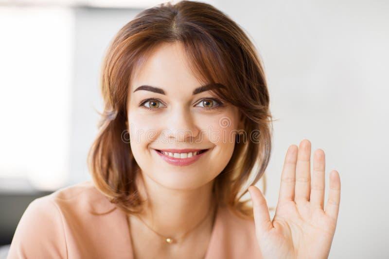 Stående av att le den vinkande handen för ung kvinna arkivbilder