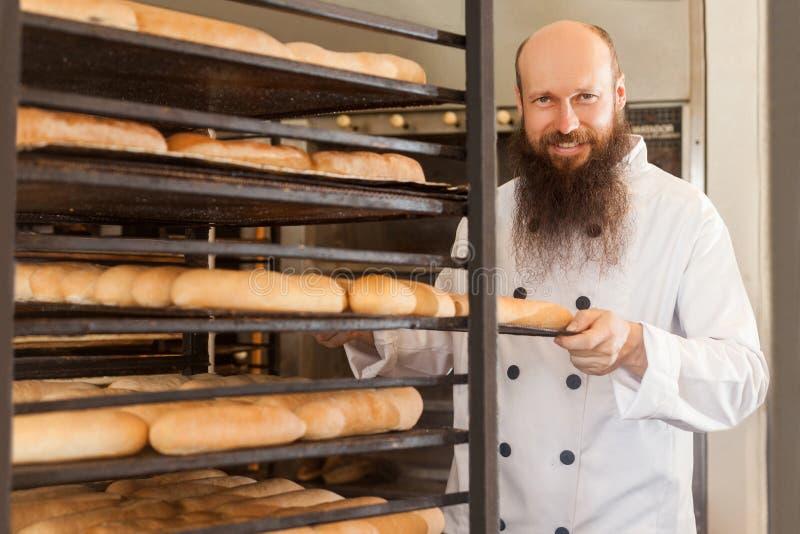 Stående av att le den vuxna bagaren med det långa skägget i det vita enhetliga anseendet i hans arbetsplats och att skjuta bakplå arkivbilder