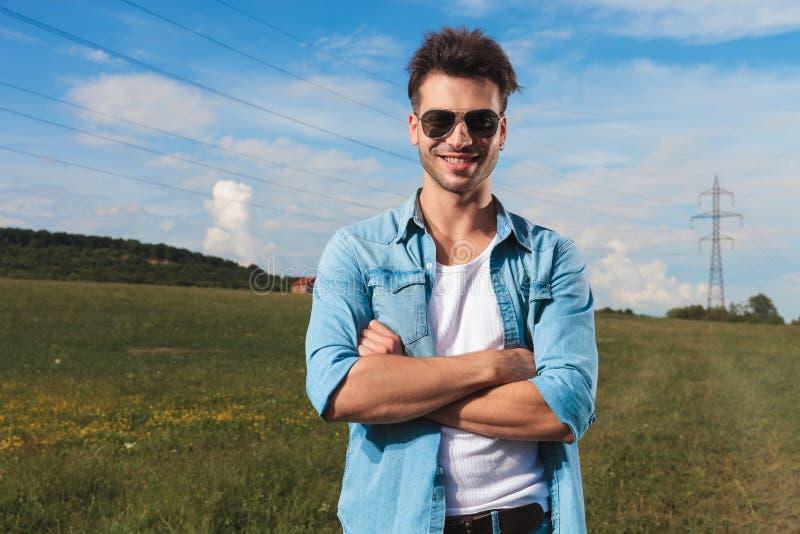 Stående av att le den stående yttersidan för tillfällig man med vikta armar fotografering för bildbyråer