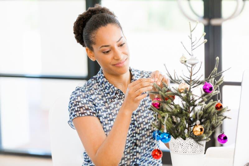 Stående av att le denamerikan kontorsarbetaren som dekorerar julträdet i offfice arkivbilder