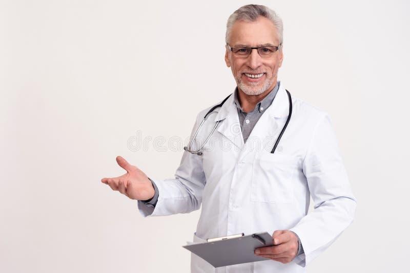 Stående av att le doktorn med den isolerade stetoskopet och skrivplattan arkivbilder