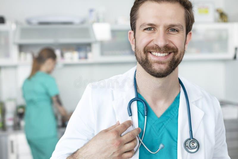 Stående av att le doktorn som står mot coworker på den veterinär- kliniken fotografering för bildbyråer