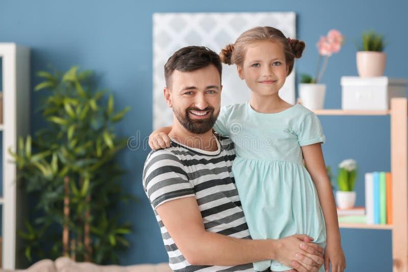 Stående av att le fadern och dottern hemma arkivfoto