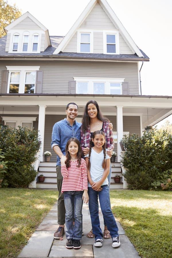 Stående av att le familjanseende i Front Of Their Home royaltyfri foto