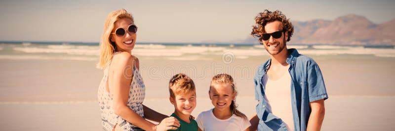 Stående av att le familjanseende på stranden arkivfoto