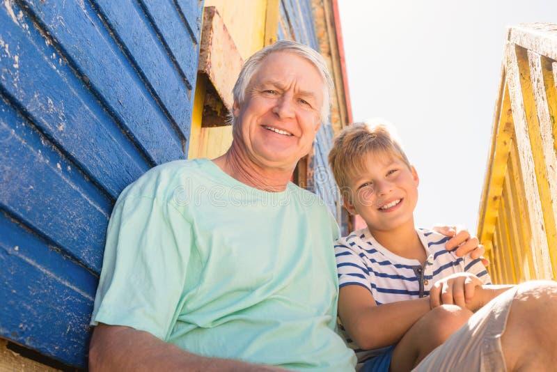 Stående av att le farfar- och pojkesammanträde på strandkojan arkivbild