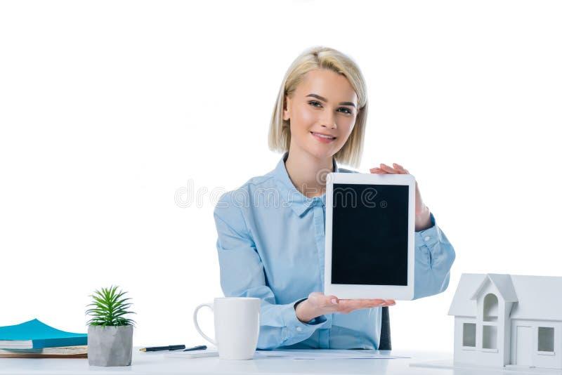 stående av att le fastighetsmäklarevisningminnestavlan på arbetsplatsen royaltyfri fotografi
