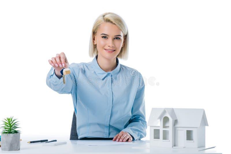 stående av att le fastighetsmäklarevisningtangenter på arbetsplatsen med husmodellen royaltyfri fotografi