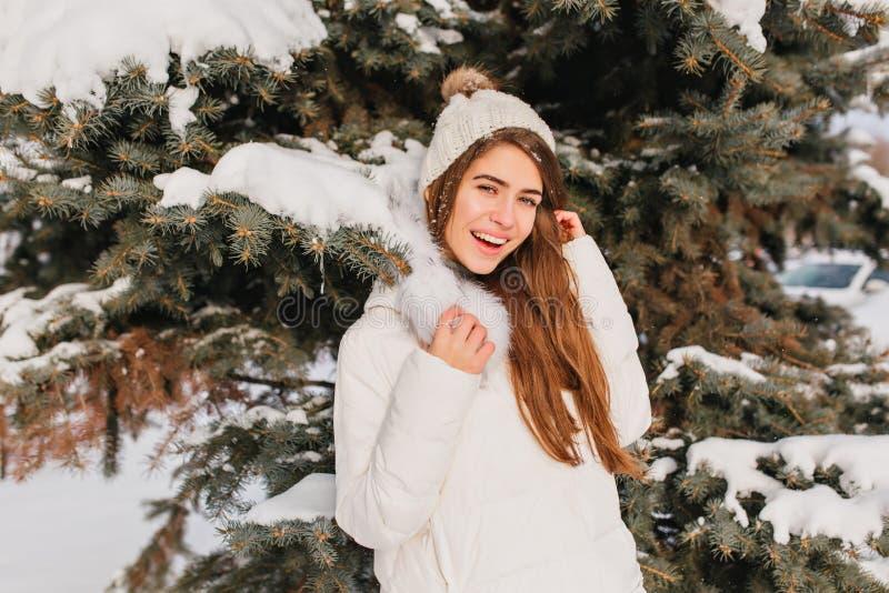 Stående av att le flickan i det varma vita laget som poserar bredvid träd i frostig dag Utomhus- foto av den romantiska damen med royaltyfria bilder