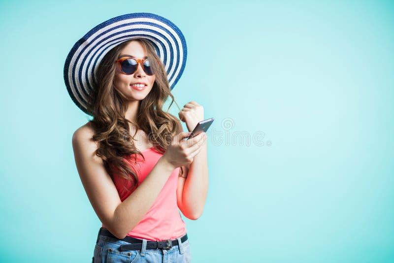 Stående av att le flickan i hatten och solglasögon, gladlynt härlig ung kvinna som pratar vid den isolerade mobiltelefonen arkivfoton