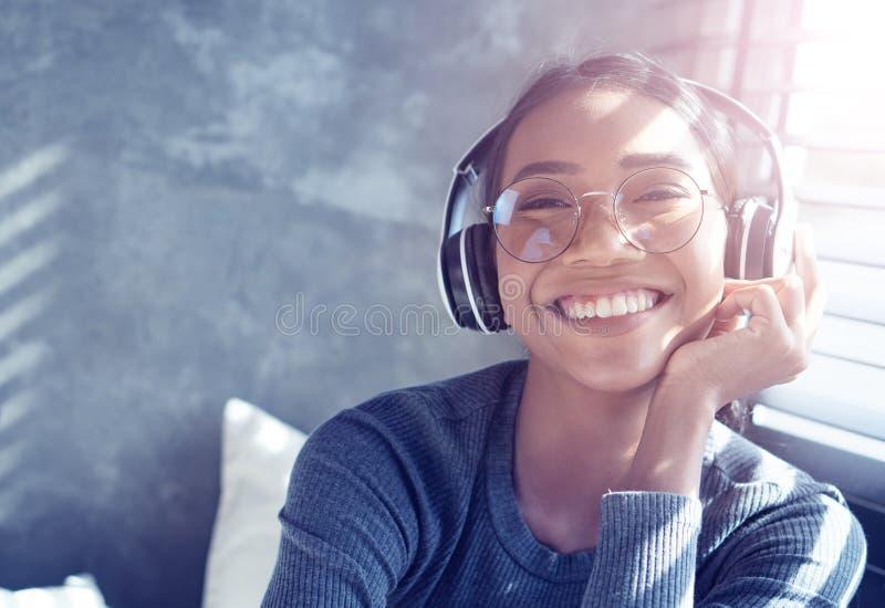 Stående av att le flickan med hörlurar som lyssnar till musik, medan sitta på soffan hemma arkivbild