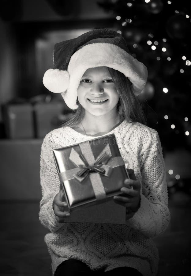 Stående av att le flickan som poserar med julklappasken royaltyfria bilder