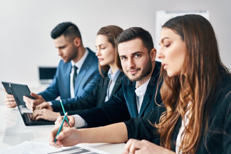 Stående av att le gruppen av affärsfolk som i rad sitter tillsammans på tabellen i ett modernt kontor arkivfoton