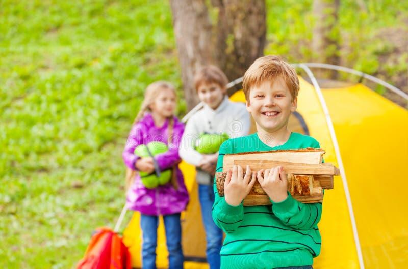 Stående av att le hållande trä för pojke för brasa royaltyfri fotografi