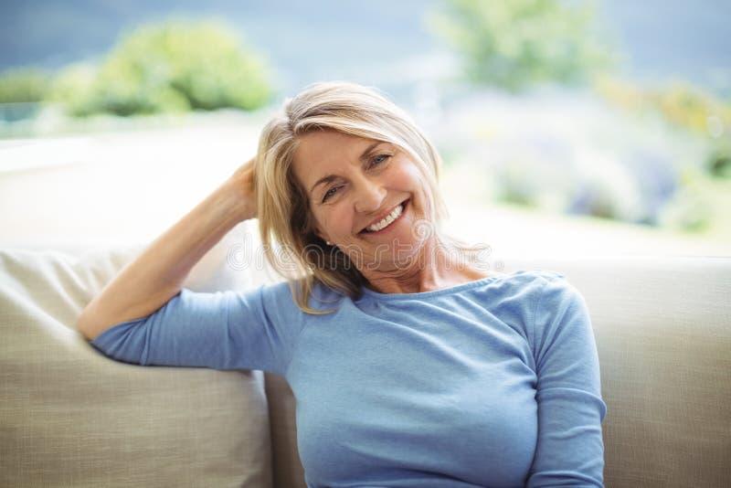 Stående av att le högt kvinnasammanträde på soffan i vardagsrum royaltyfria foton