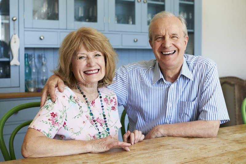 Stående av att le högt parsammanträde på Sofa At Home royaltyfri bild