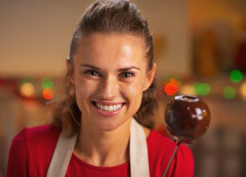 Stående av att le hemmafruvisningäpplet i chokladglasyr royaltyfri foto