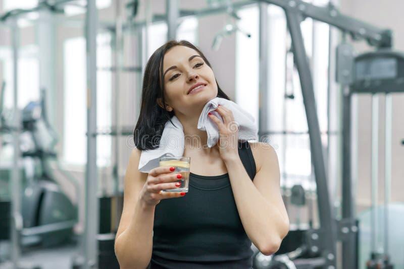 Stående av att le konditionkvinnan med exponeringsglas av vatten med citronen, kvinna i sportswear efter konditiongruppdricksvatt arkivfoto