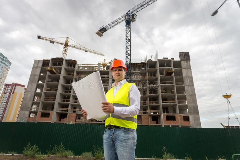 Stående av att le konstruktionsteknikern som poserar med ritningar mot byggnad under konstruktions- och arbetekranar arkivbild