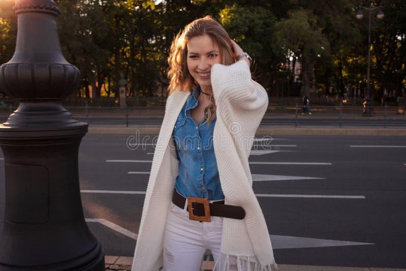 Stående av att le kvinnan i en vit kofta royaltyfri fotografi
