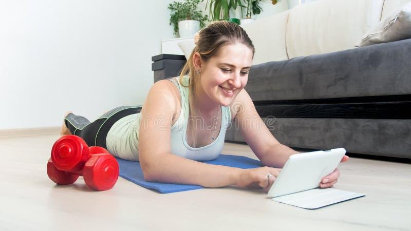 Stående av att le kvinnan med den digitala minnestavlan som ligger på golv arkivfoto