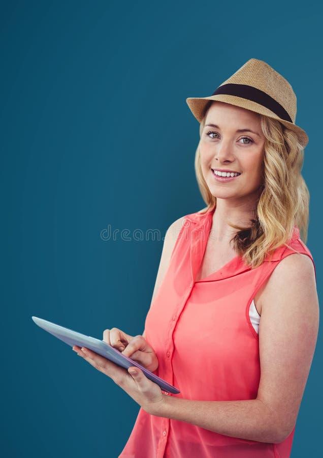 Stående av att le kvinnan som rymmer den digitala minnestavlan mot blå bakgrund royaltyfri foto