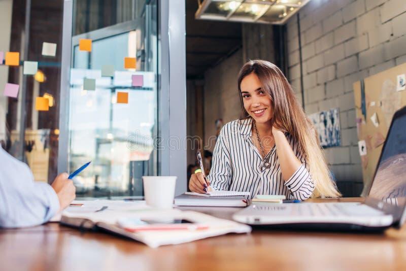 Stående av att le kvinnlig handstil för kontorsarbetare som ser kamerasammanträde på konferensrum under mötet arkivbild