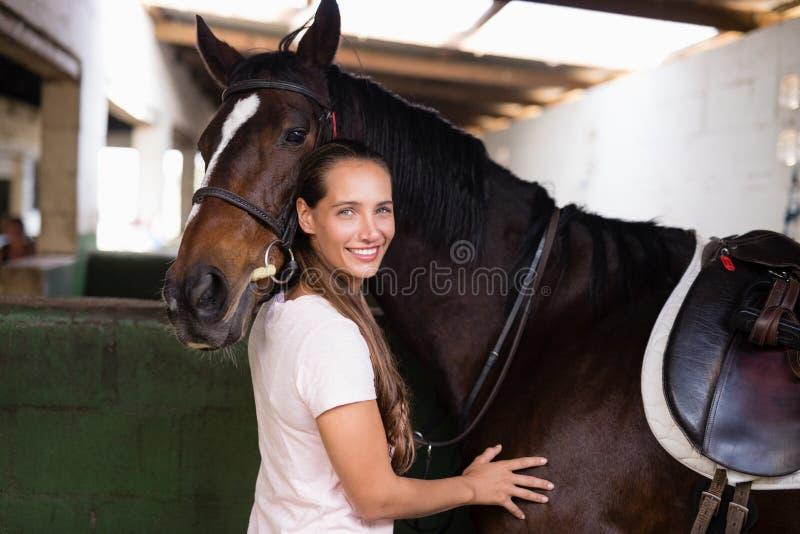Stående av att le kvinnligt jockeyanseende vid hästen royaltyfri bild