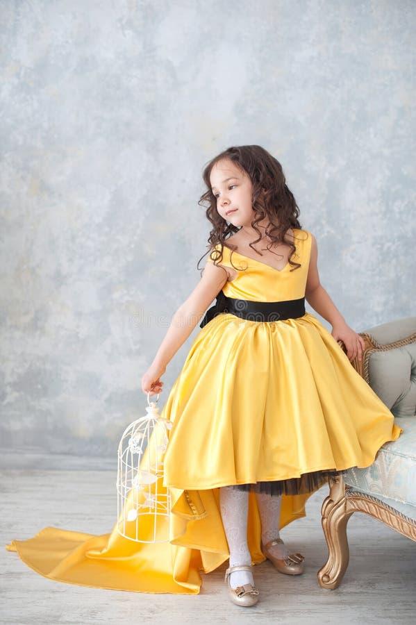 Stående av att le lilla flickan i guld- klänning för prinsessa med fjärilar royaltyfria bilder